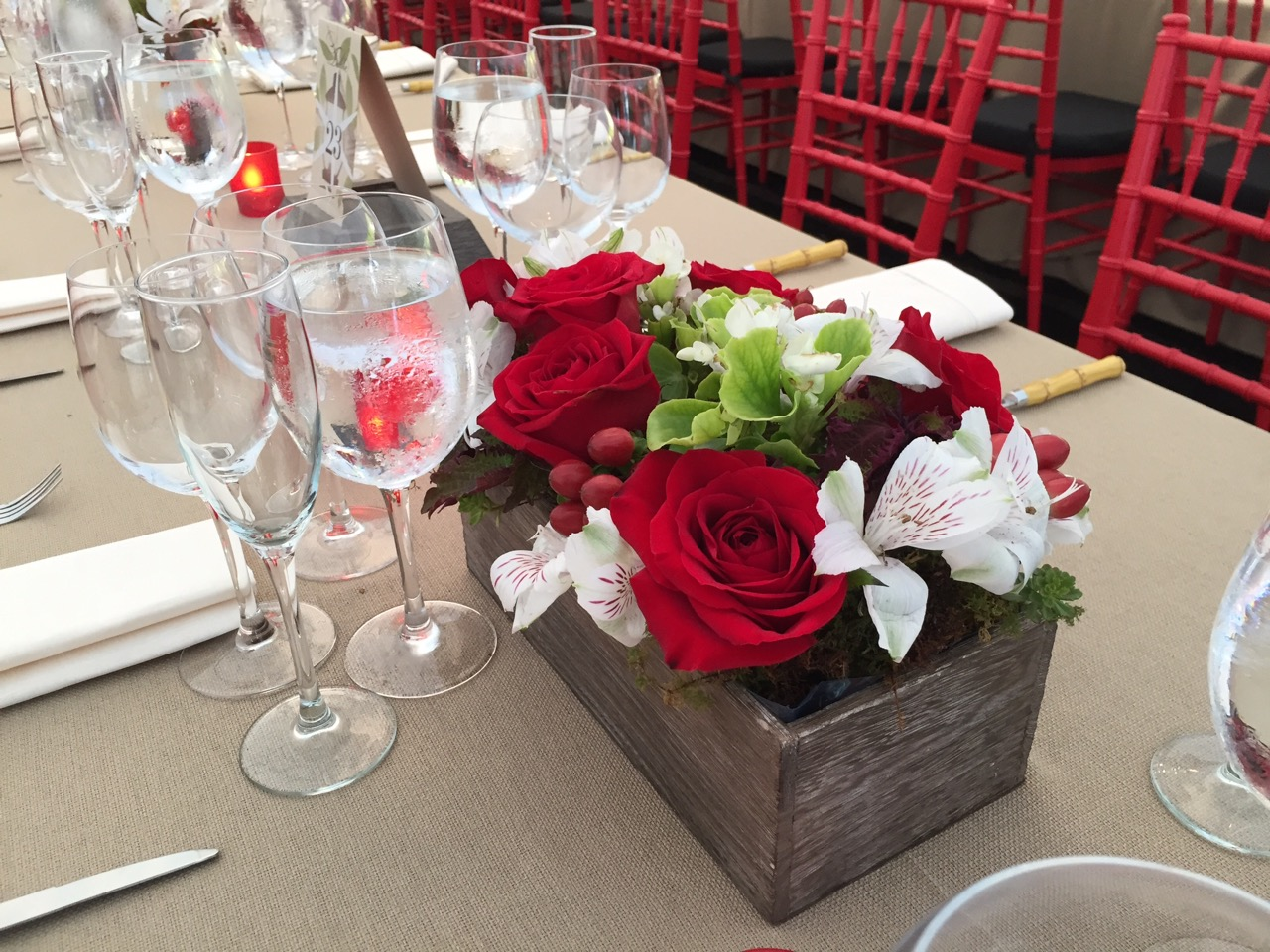 Rustic, garden box-inspired centerpieces with red roses, hypericum and live rooted floral accents