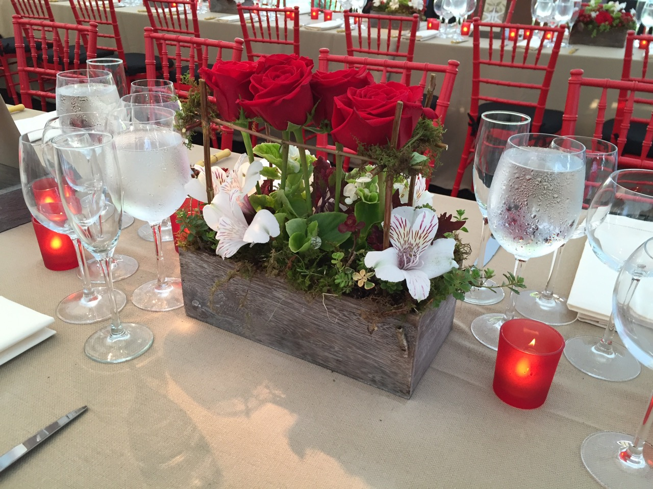 Tablescape with faux burlap linens, red frosted candle holders, and red chiavari chairs