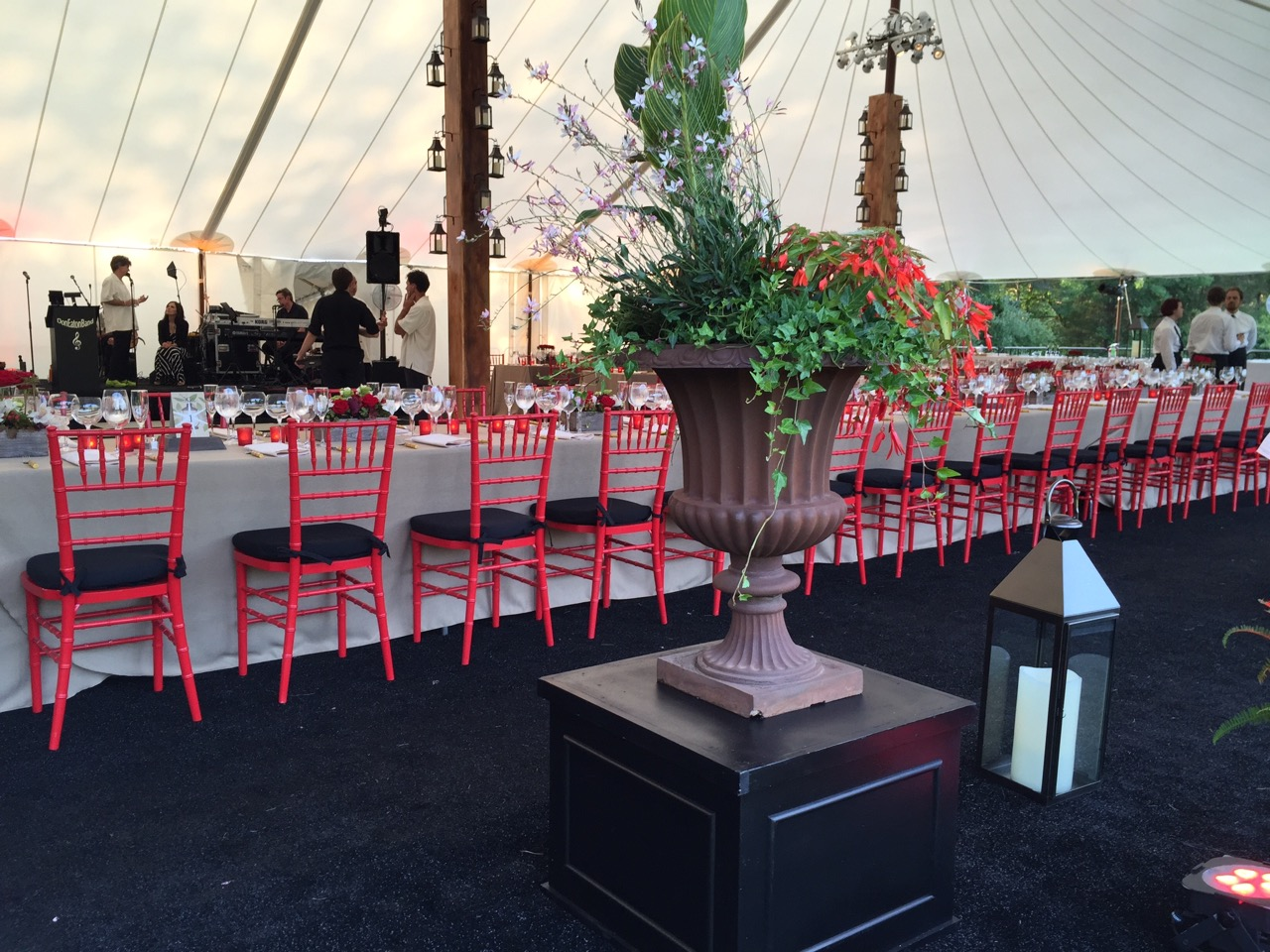 Large floor lanterns, entryway urns with live flowers and foliage, and the long head table