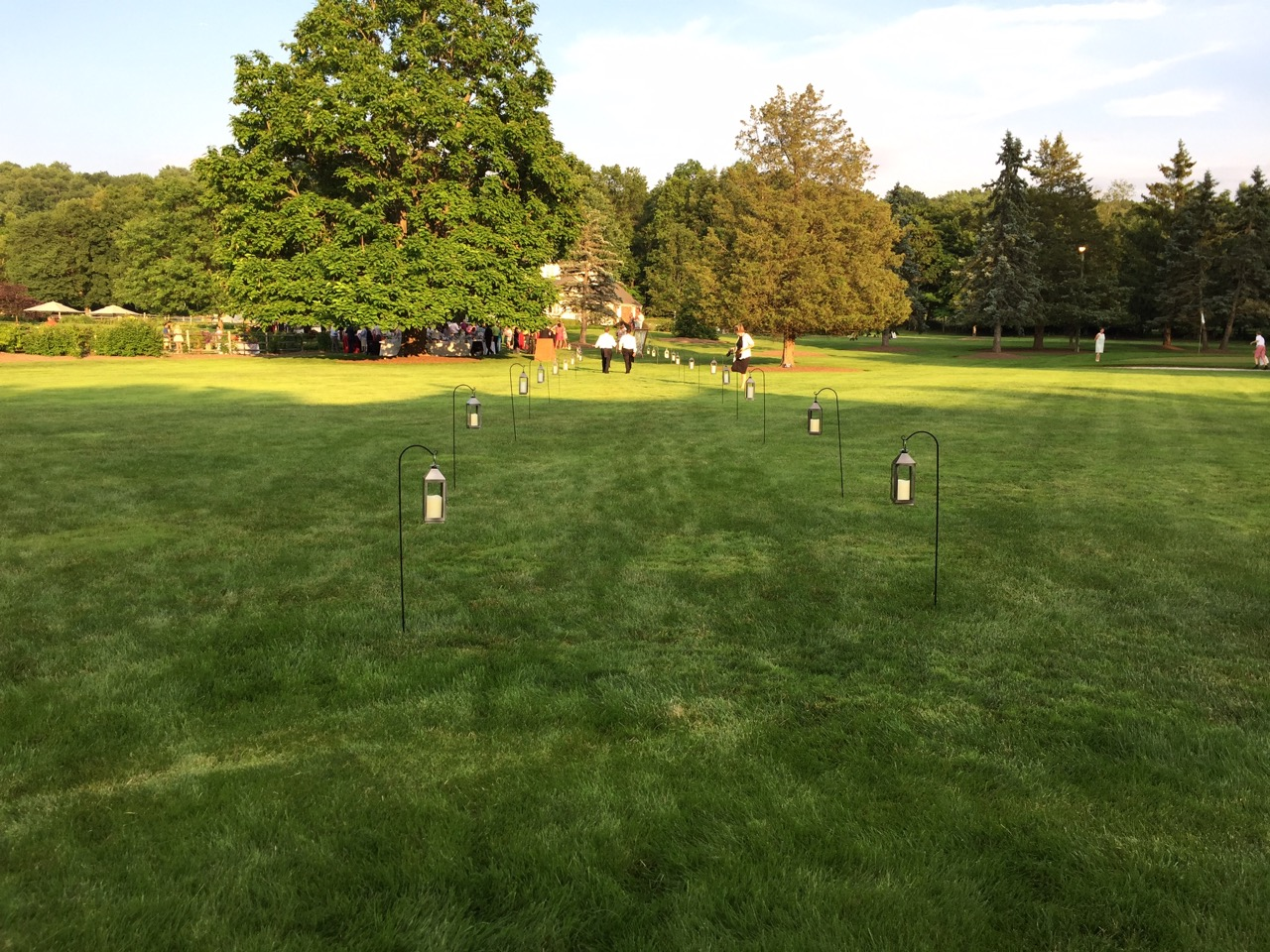 The view from the tent to the house and cocktail area, lined with lanterns on shepherd's hooks