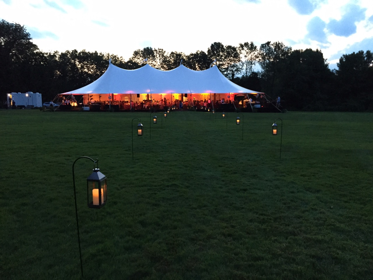 The view from the walkway to the tent entry at dusk, with amber uplighting in the tent