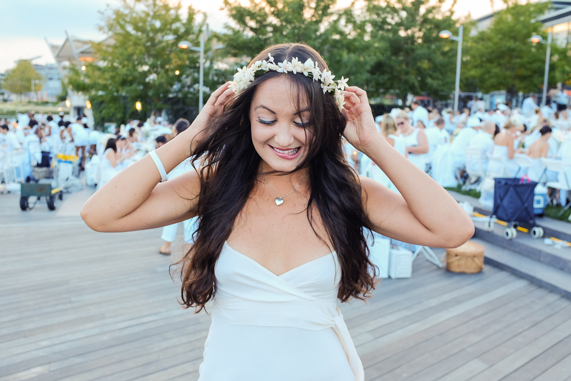 Fran Holuba of the White House adjusts her flower crown at the inaugural Diner En Blanc event in Washington, DC on a perfect summer evening.