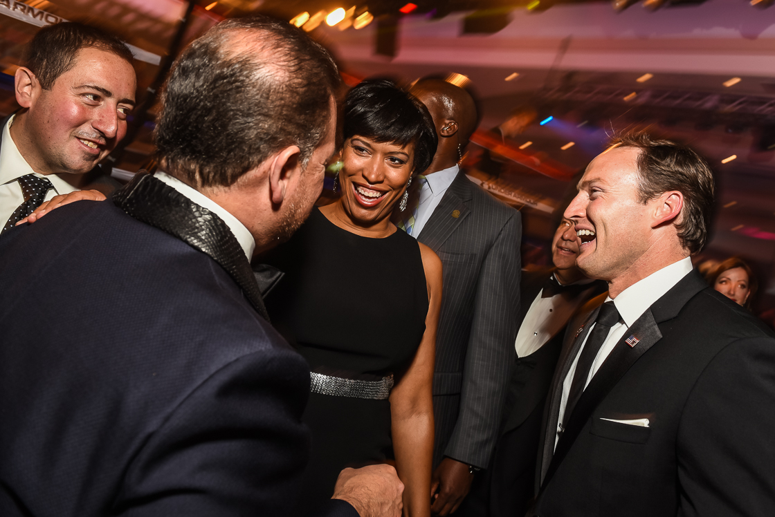 Mayor-elect Muriel Bowser laughs with male business leaders during pre-fight cocktails.