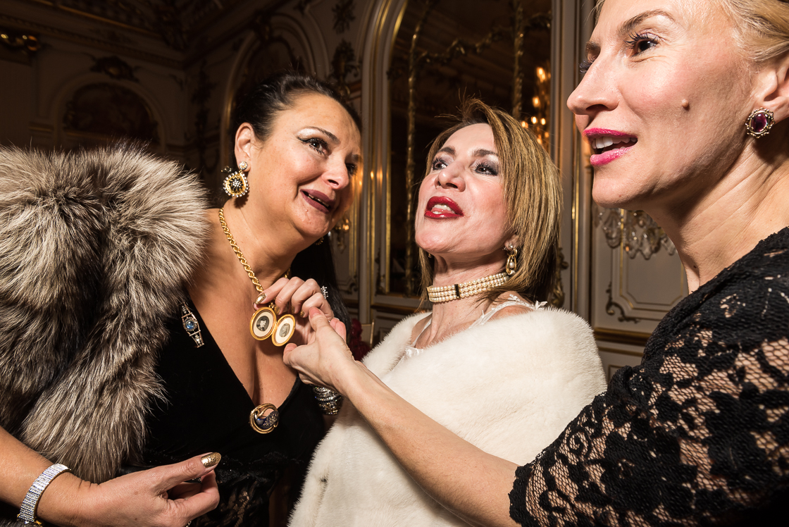 Diplomatic Liaison Rhoda Septilici, left, shows off a photo of her great grandmother, who is wearing the same brooch she has on here at the January 10 Russian Ball. Leila Beale, wife of the Barbados ambassador (center), and Gabriela Coman (right) inspect the photo.
