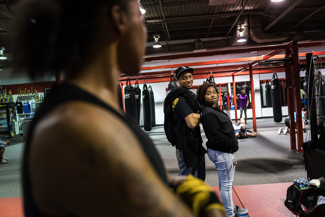 Nelson watches a training match with her children Simone and Q nearby. As a single mother on a fixed income, she has brought them to the gym with her every day for the last 10 years.