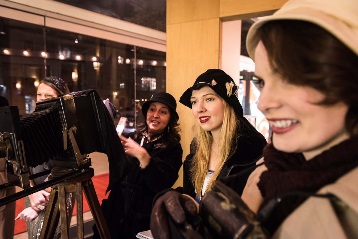 Volunteer actresses Lelia TahaBurt, Megan Konyndyk, and Jessica Inzeo (from left) perform as friendly paparazzi to guests as they arrive.