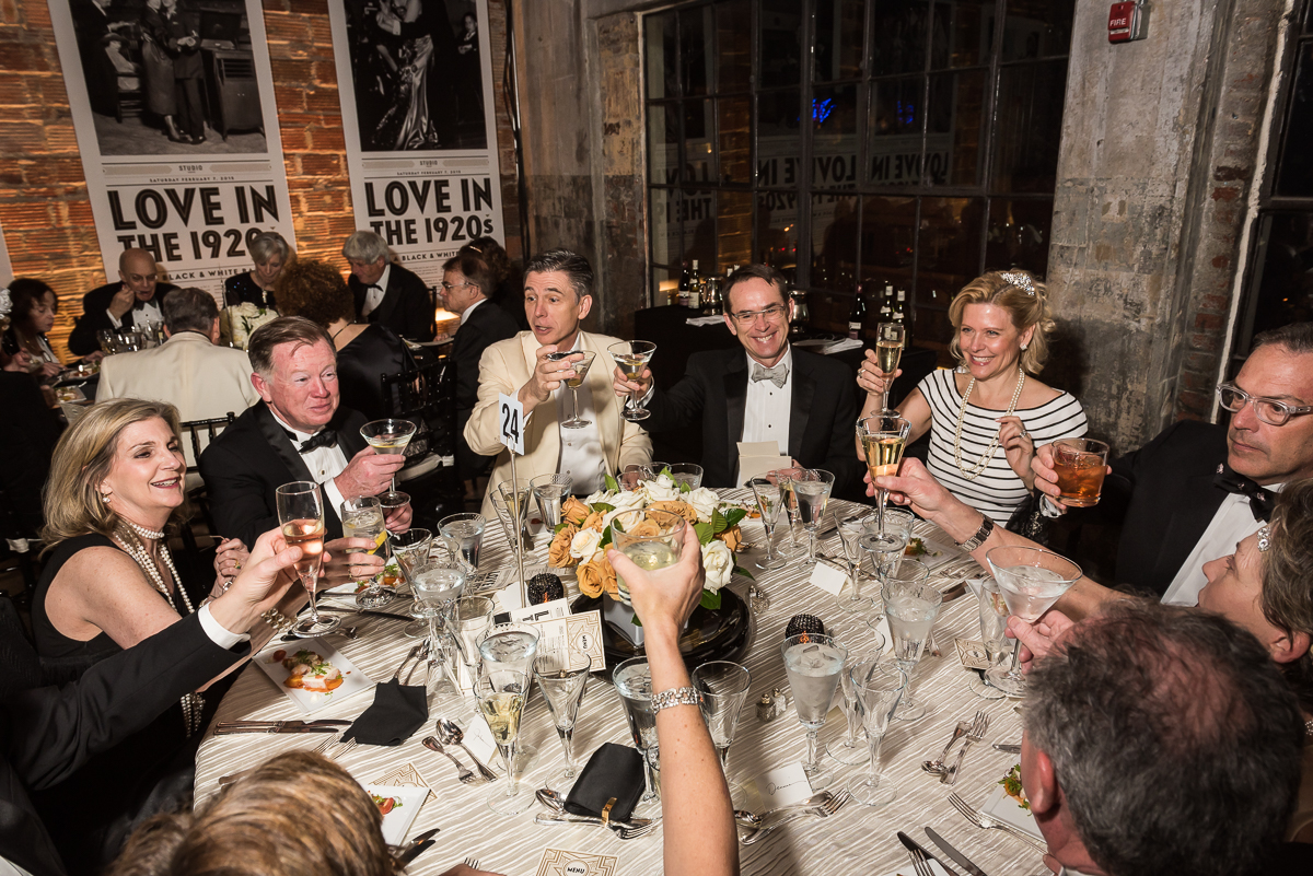 A table of Studio Theater Gala guests raise their glasses to cheers a successful event.