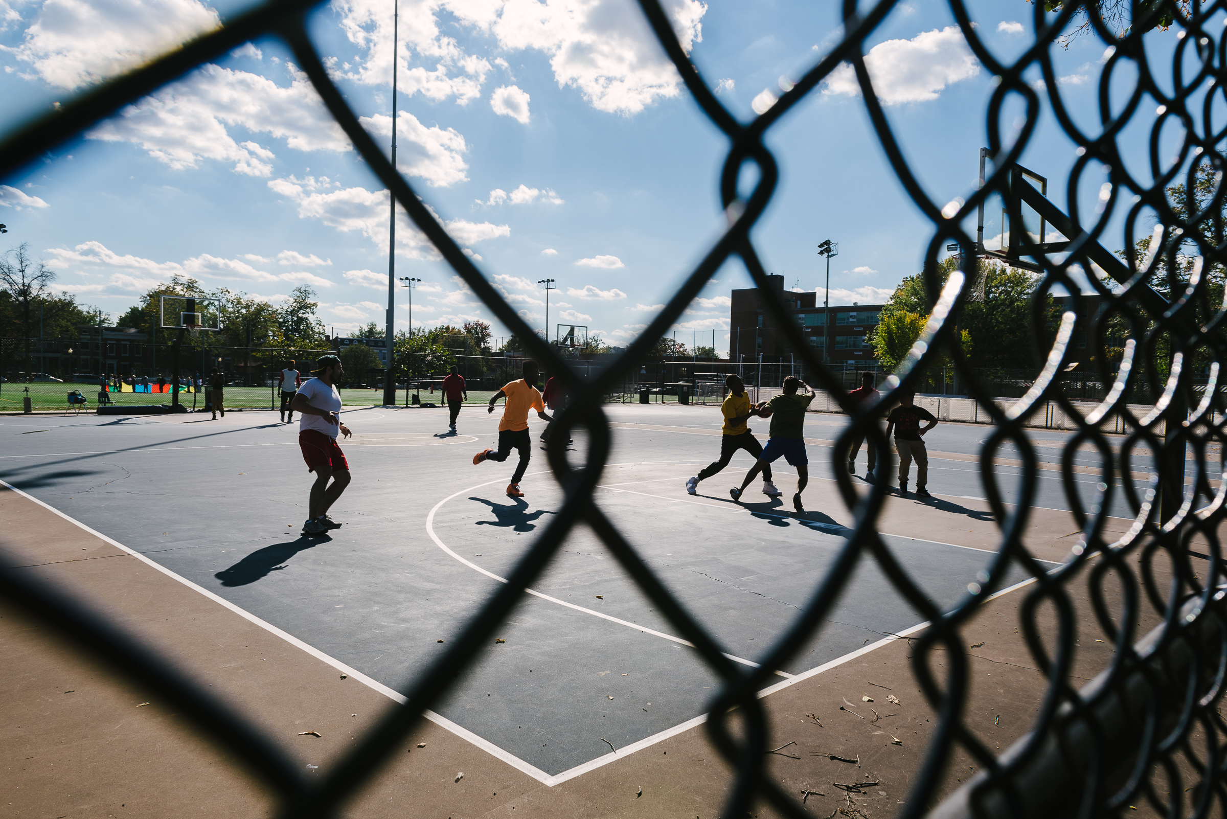 Neighborhood resident play basketball on the courts built when the new school was built next door to the old one. Often, new buildings are constructed instead of preserving the old ones as a cost-cutting measure, leaving historic structures to rot in vacancy.