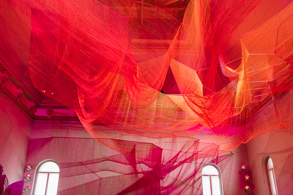 Janet Echelman's woven textile installation mirrors the affects of an earthquake through suspended nets and a corresponding carpet below.