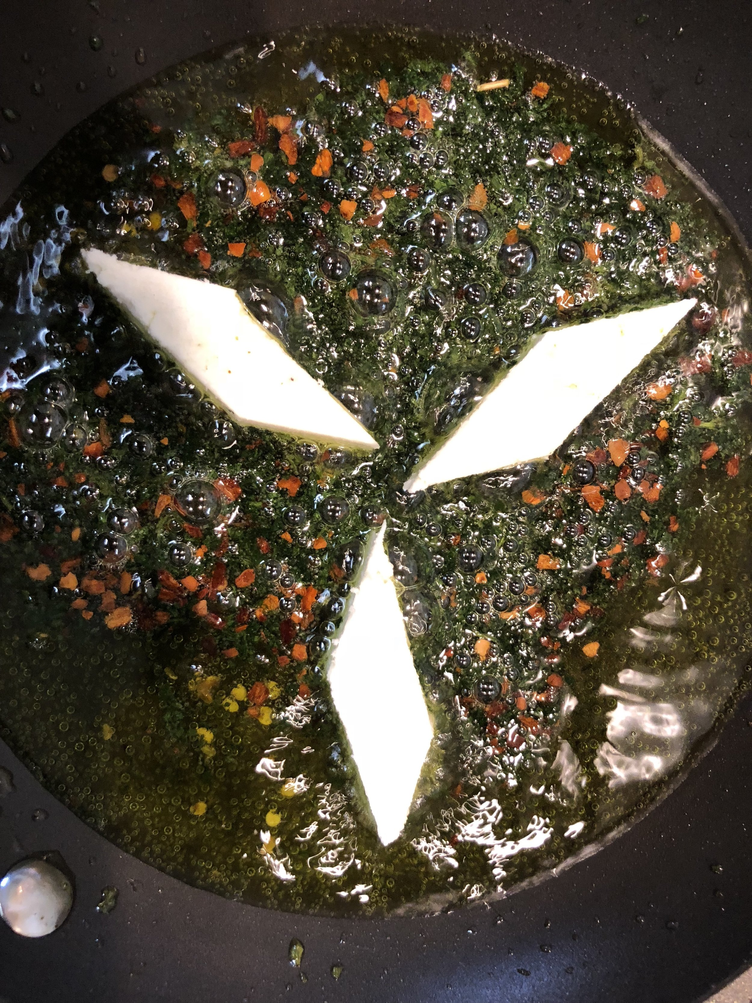 Pan frying the paneer cheese in cilantro-red chili oil.