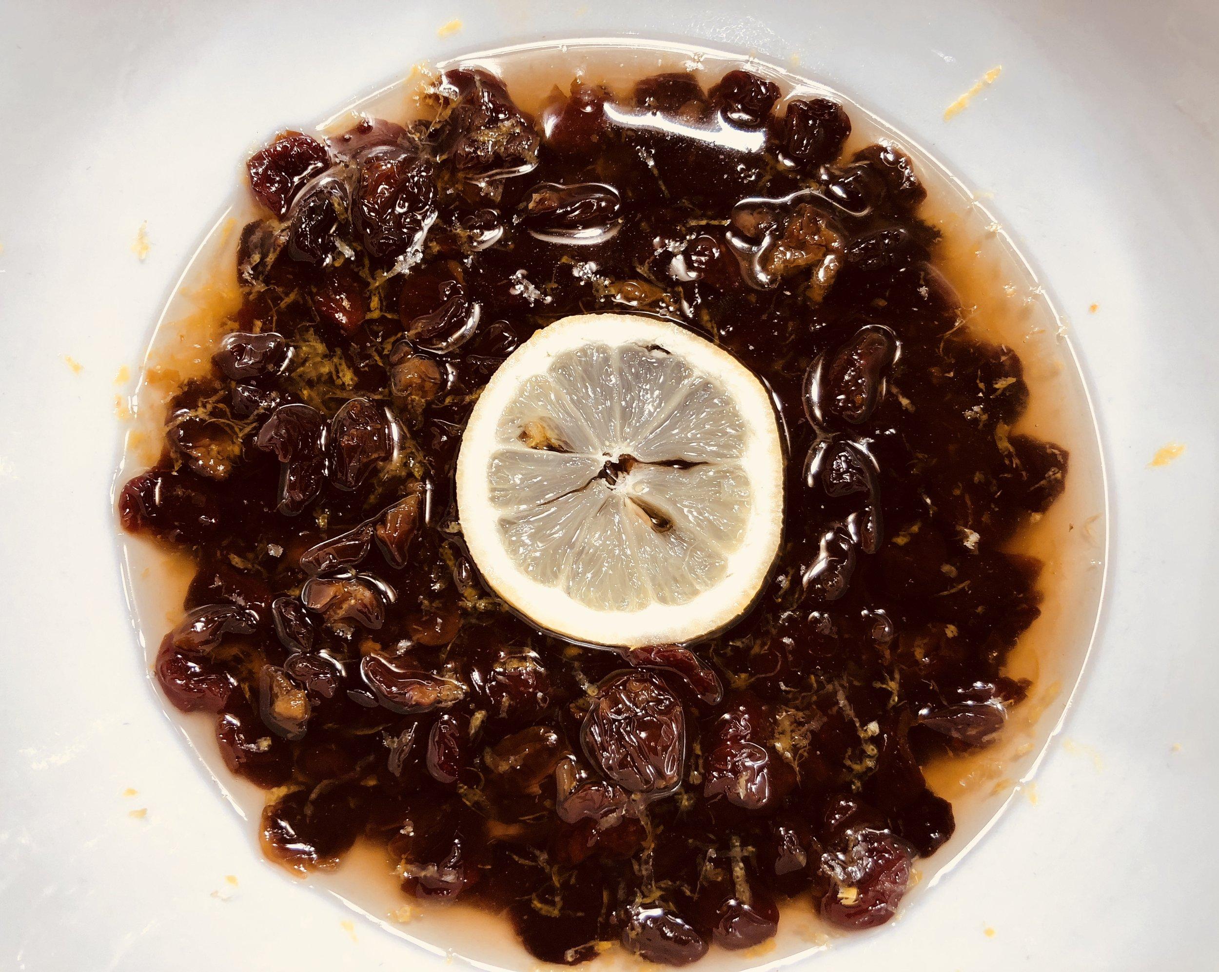 Marinating the dried cherries with lemon zest, vanilla, and sugar.