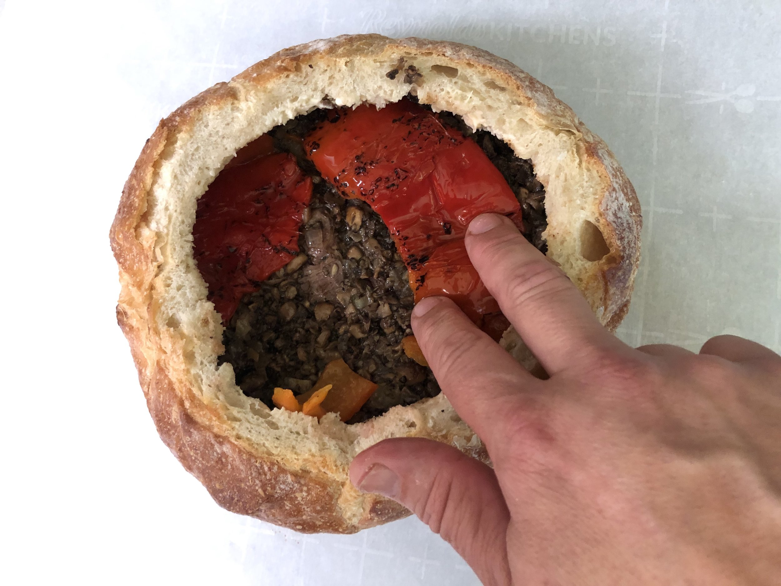 Layer in the steak, duxelles, then roasted red bell pepper, making sure to cover the entire diameter of the bread bowl.