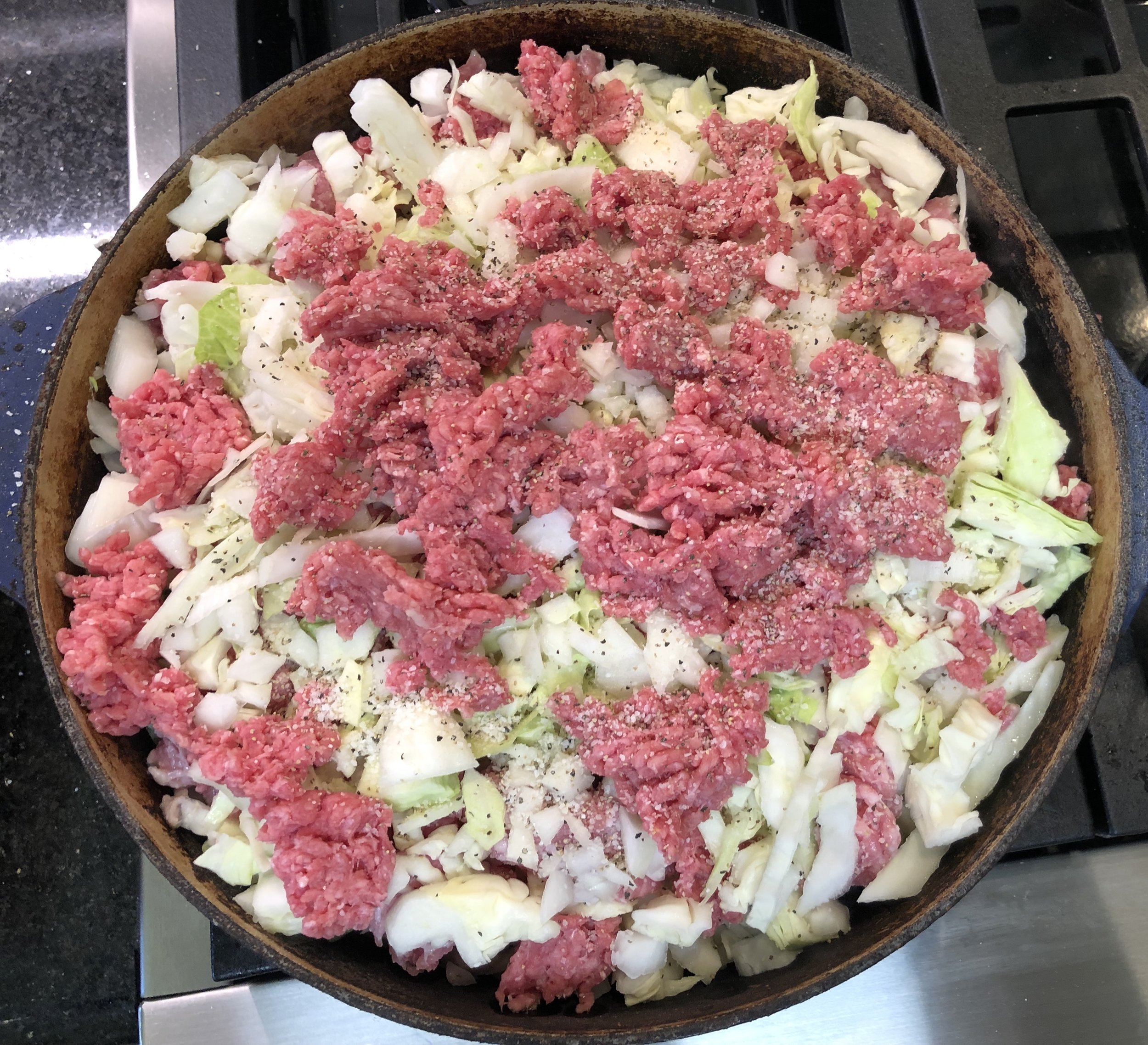 Layering the cabbage, onion, and meat to slowly braise.