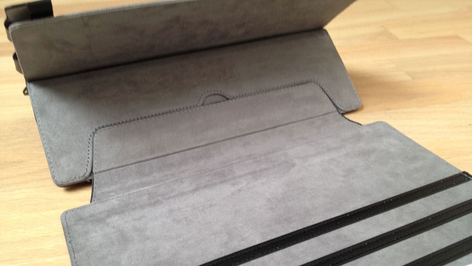 Both covers adhere to the frame with a wide velcro tab. The flap on the frame folds out to provide great stability when the case is opened. The Surface Pro sits much more firmly in one's lap when used in this manner (see gif animation below).