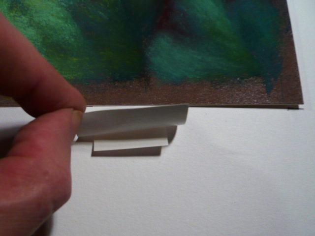 Making tape hinge. Affix one piece of tape to upper back edge of artwork. Use a second piece to attach the first tape to the board.