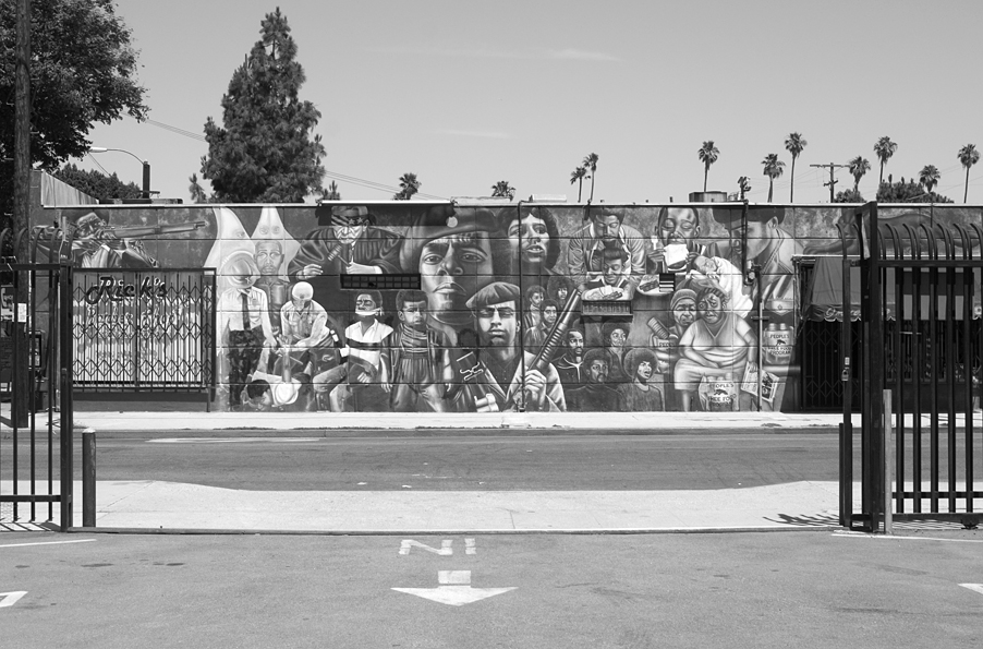 """Noni Olabisi's 1995 mural """"To Protect and Serve,"""" painted on the wall of a building in Crenshaw that is also home to a barber shop and a hair salon. The mural (commissioned by SPARC and paid for by private funds after city funding fell through), illustrates violence and injustice against Black people in the US, and the militant and community-serving aspects of the Black Panther Party for Self Defense (BPP), ending with a listing of the BPP's Ten-Point Program. 2008. Copyright Noni Olabisi.                                0     false             18 pt     18 pt     0     0         false     false     false                                                     /* Style Definitions */ table.MsoNormalTable {mso-style-name:""""Table Normal""""; mso-tstyle-rowband-size:0; mso-tstyle-colband-size:0; mso-style-noshow:yes; mso-style-parent:""""""""; mso-padding-alt:0in 5.4pt 0in 5.4pt; mso-para-margin:0in; mso-para-margin-bottom:.0001pt; mso-pagination:widow-orphan; font-size:10.0pt; font-family:""""Times New Roman"""";}"""