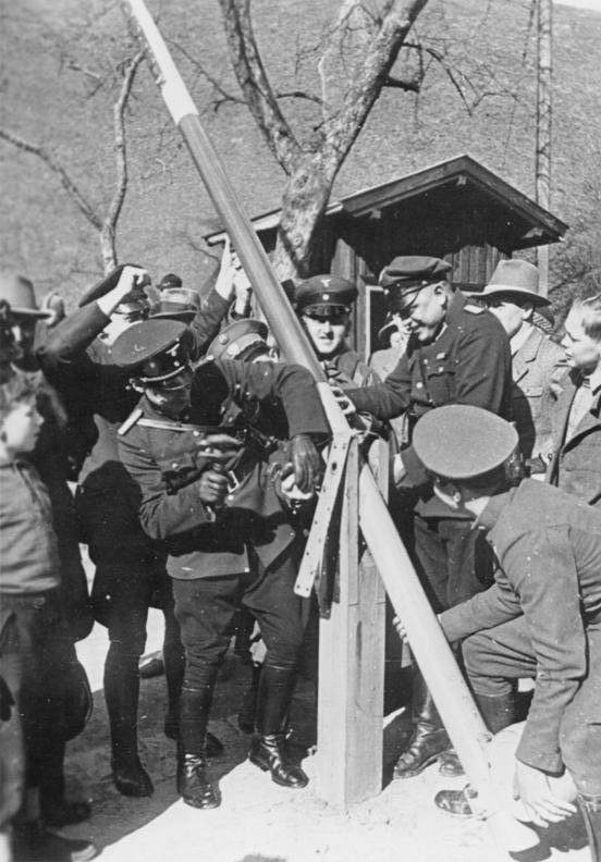 Click photo to download. Caption: German and Austrian border police dismantle a border post on March 15, 1938. Credit: German Federal Archives.