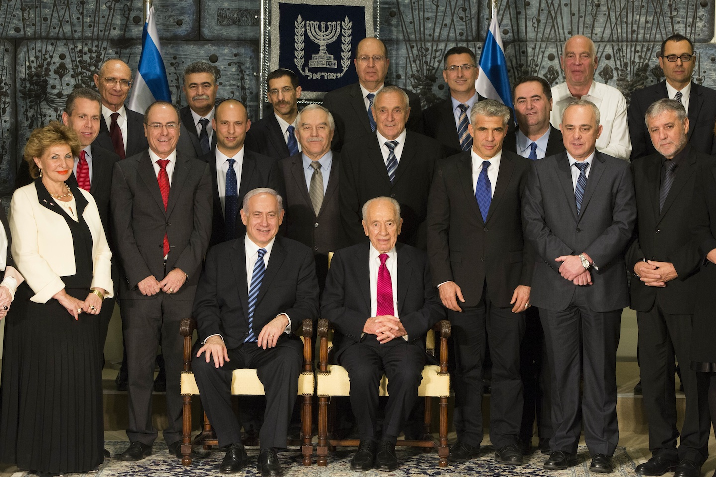 Click photo to download. Caption: Israeli President Shimon Peres (C, seated) sits next to Prime Minister Benjamin Netanyahu (L, seated) as they pose for a group photo together with the ministers of the new Israeli government, in Jerusalem, on March 18, 2013. The new government comprises four parties: Prime Minister Benjamin Netanyahu's Likud-Beiteinu alliance, Naftali Bennett's Jewish Home, Yair Laipd' Yesh Atid, and Tzipi Livni's Hatnuah. Credit: Yonatan Sindel/Flash90.