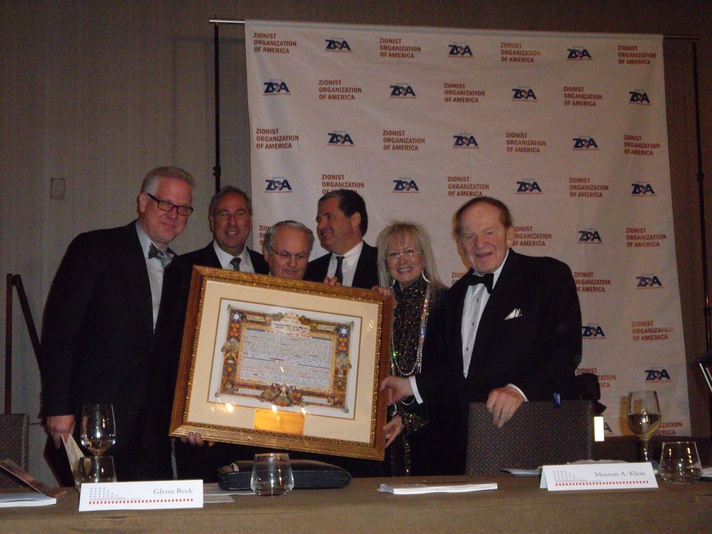 Click photo to download. Caption: Far left, star broadcaster Glenn Beck, recipient of the first Dr. Miriam & Sheldon Adelson Defender of Israel Award. Far right and second from right, Sheldon and Miriam Adelson. Holding the award is Zionist Organization of America President Mort Klein. Credit: Jacob Kamaras.