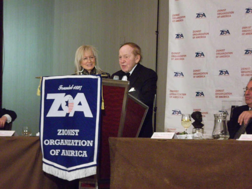 Click photo to download. Caption: Dr. Miriam and Sheldon Adelson share the podium at Sunday night's Zionist Organization of American gala in New York City. Credit: Jacob Kamaras.