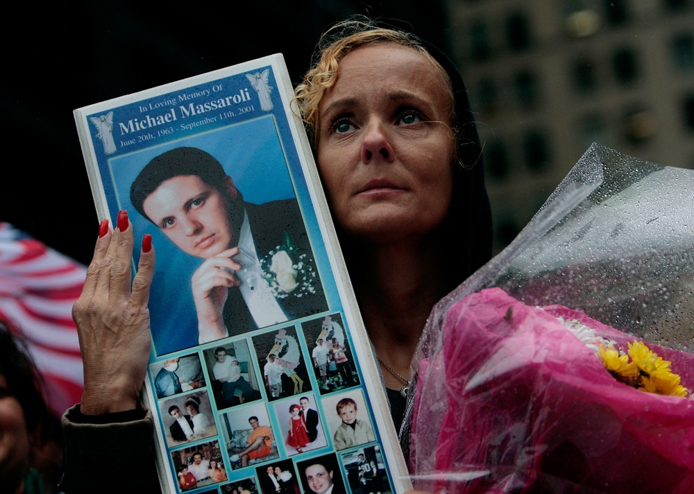 Click photo to download. Caption: Diane Massaroli (R), of Staten Island, New York holds up a picture of her late husband, Michael Massaroli, who worked at Cantor Fitzgerald at the World Trade Center, as his name is read at Ground Zero during a 9/11 memorial ceremony in New York City on Sept. 11, 2009. Credit: EPA/CHRIS HONDROS/POOL.