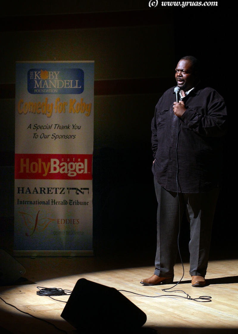 """Click photo to download. Caption: Comedian Saleem Muhammad performs at a """"Comedy for Koby"""" show. Credit: Yissachar Ruas."""