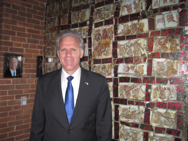 """Click photo to download. Caption: Amb. Michael Oren in front of artwork titled """"Shalom"""" at the Banneker Douglass Museum of African American history in Annapolis, Md., with a photo of Maryland Governor Martin O'Malley in the background. Credit: Paul Foer."""