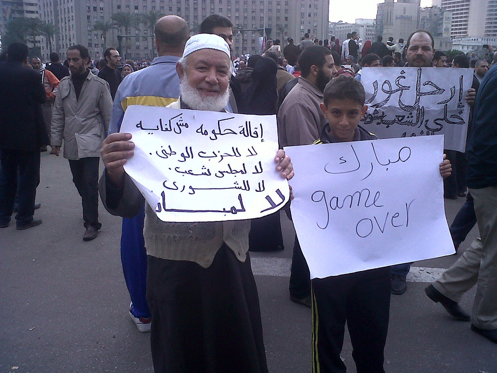 """Click photo to download. Caption: (From left to right) In Egypt on Jan. 30, 2011, one protester's sign reads """"The stepping down of the government is not enough.. No to the NDP, No to the MPs.. No to Mubarak,"""" and the other's reads """"Mubarak Game Over."""" Credit: BanyanTree."""