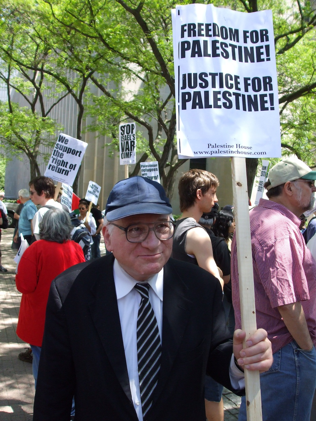 """Click photo to download. Caption: Danny Goldstick holding a """"Freedom For Palestine!"""" sign at a demonstration accusing Israel of apartheid. The New Israel Fund has cut off funding to several groups that demonize Israel, but has continued to fund others, according to JNS columnist Gerald Steinberg. Credit: Johan1917/Wikimedia Commons."""