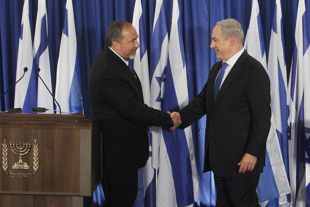 Click photo to download. Caption: Prime Minister Benjamin Netanyahu of the Likud party (R) and Foreign Minister Avigdor Lieberman of the Yisrael Beiteinu party shake hands at a joint press conference Oct. 25 announcing that the two parties are joining forces ahead of the upcoming Israeli general elections. Credit: Miriam Alster/FLASH90.