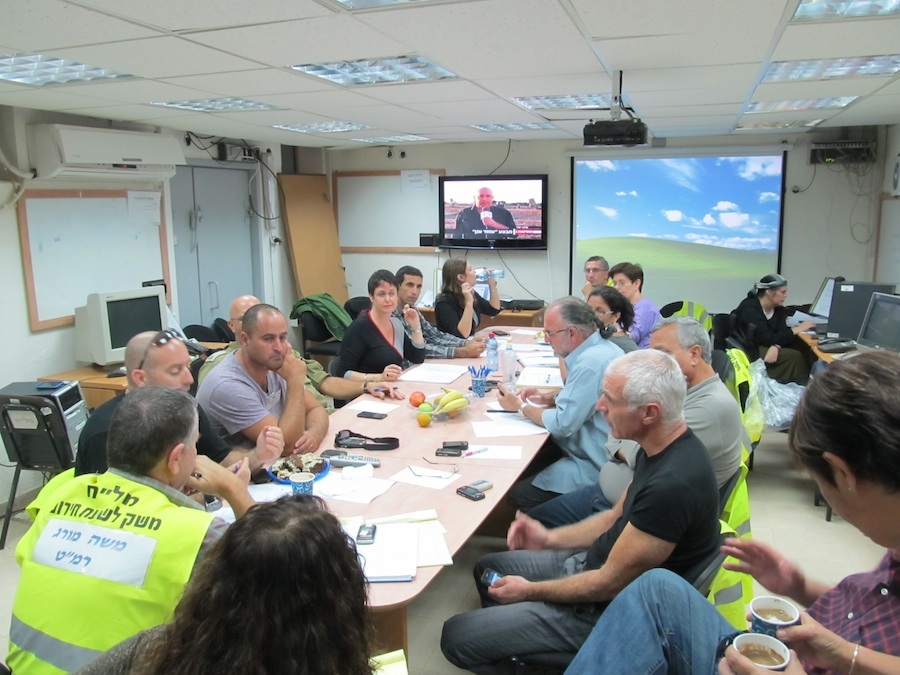 """Click photo to download. Caption: The """"situation room"""" of the Eshkol Municipal Council. This meeting—including all the department heads in the council (security, education, care of population, engineering, agriculture, public information)—takes place twice a day to understand the needs of area residents and search for solutions amid rocket attacks. Credit: Ronit Minaker."""