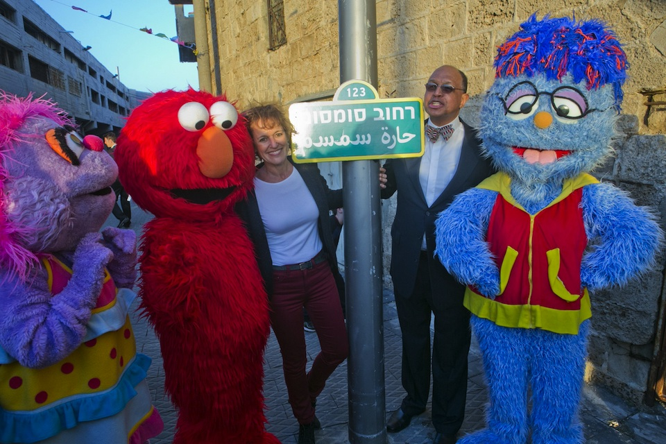 Click photo to download. Caption: Avigail, Elmo, Alona Abt (Rehov Sumsum's director on its set in Herzliya), Melvin Ming (president and CEO of Sesame Workshop), and the Arab Israeli character Mahboub. In center in the Rehov Sumsm (Sesame Street) sign. Credit: D Guthrie.