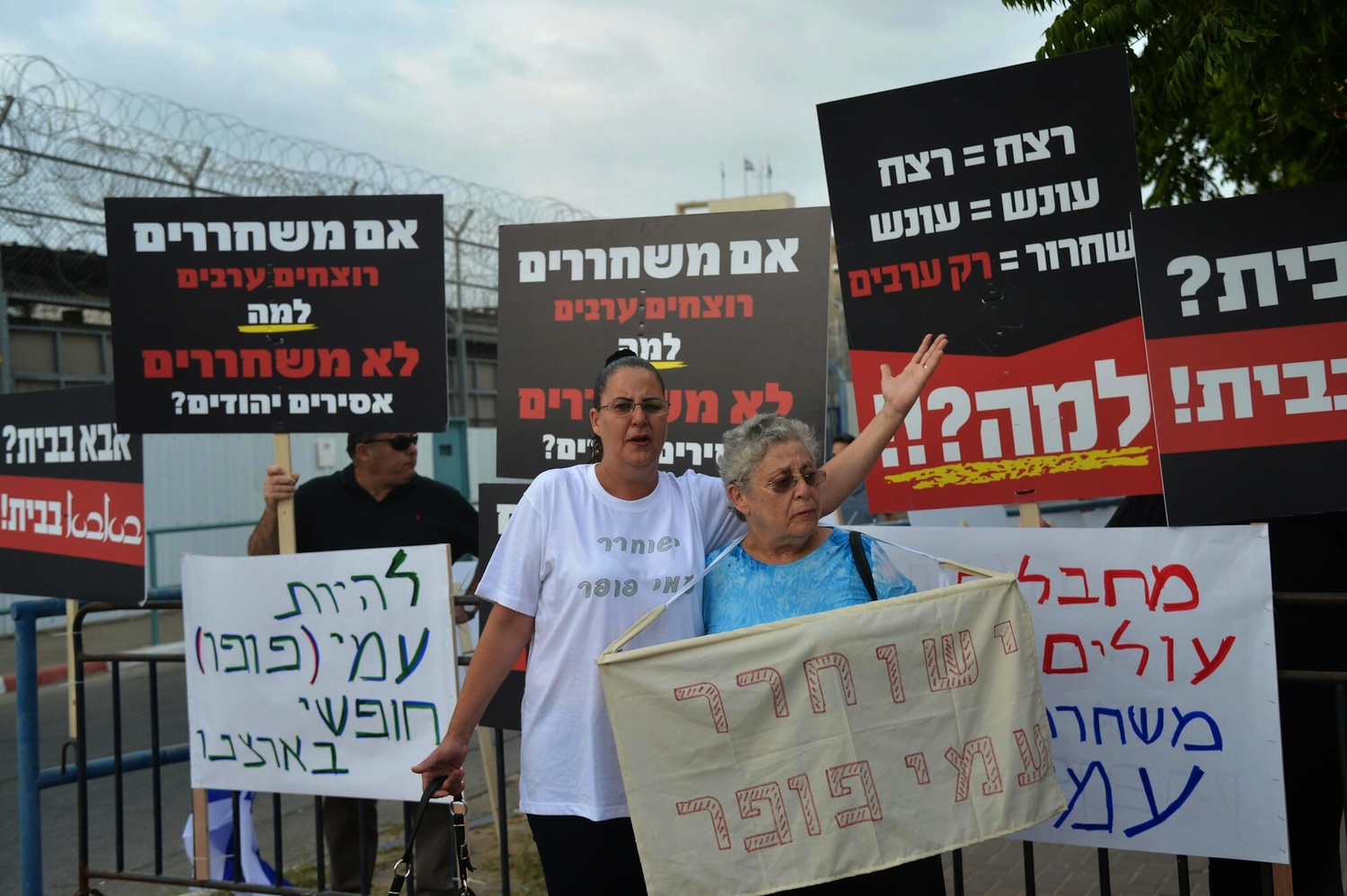 Click photo to download. Caption: Relatives of Israelis killed in terror attacks hold signs as they protest the release Palestinian prisoners for Israel-Palestinian conflict negotiations on August 13, 2013, outside Ayalon prison near Ramle. Credit: Yossi Zeliger/Flash90.