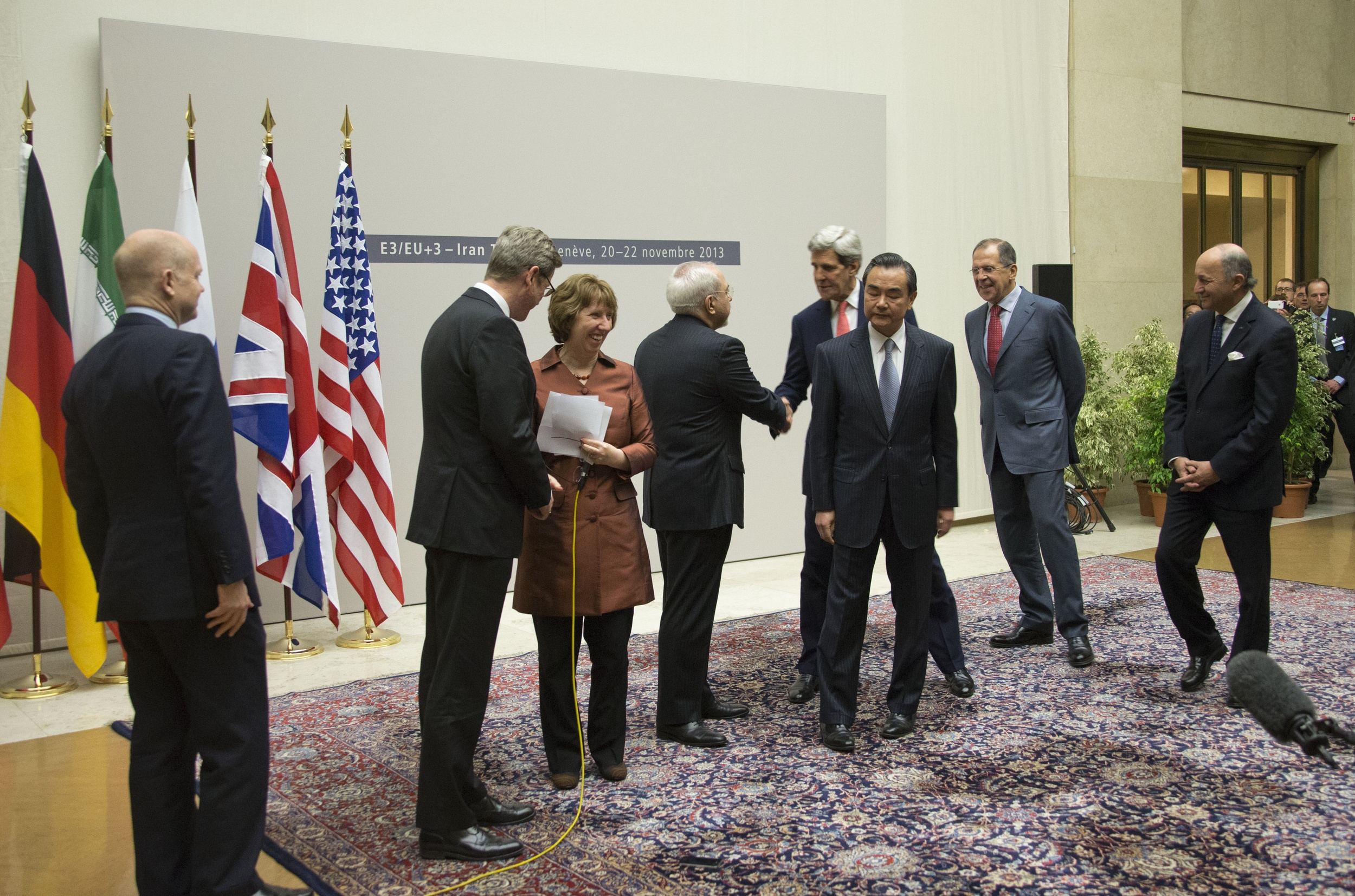 Click photo to download. Caption: U.S. Secretary of State John Kerry (pictured at center) shakes hands with Iranian Foreign Minister Javad Zarif after the P5+1 powers and Iran concluded negotiations on the Iran nuclear program on November 24, 2013. Credit: U.S. Department of State.