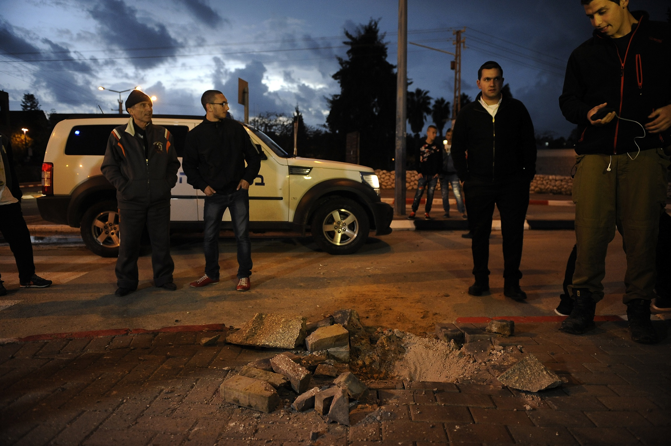 Click photo to download. Caption: Israelis stand near a hole caused by a Palestinian rocket fired from Gaza into the southern Israeli city of Sdeort on March 12, 2014. At least 60 Islamic Jihad rockets were launched from Gaza at Israel from March 12-13. Credit: Flash90.