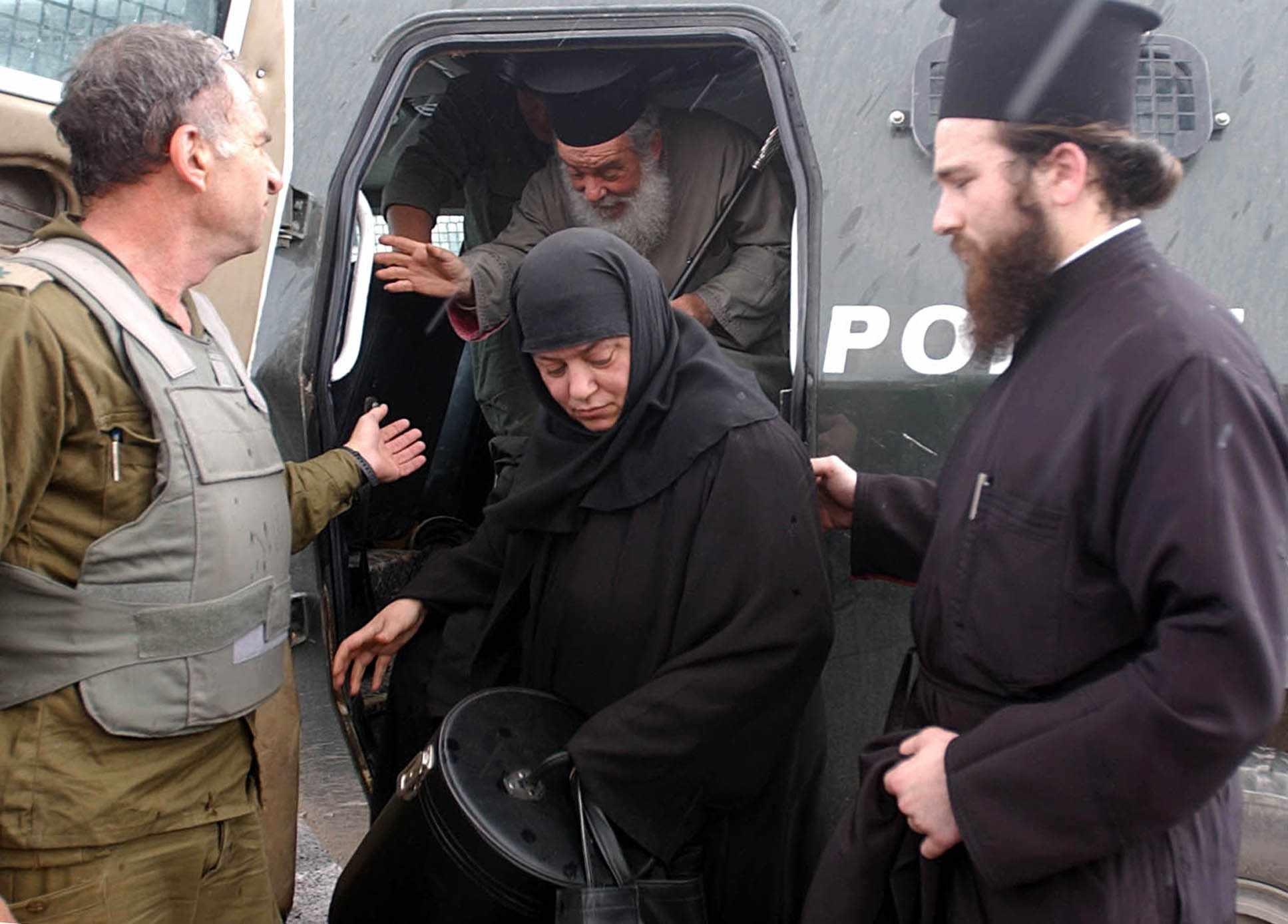 Click photo to download. Caption:An Israeli soldier helps to smuggle out a priest and a nun from the Church of the Nativity in Bethlehem on April 7, 2002. That year,a siege by Palestinian militants on the Church of the Nativity persisted from April 2 to May 10—just days after Easter on the Eastern Orthodox calendar.Credit: Flash90.