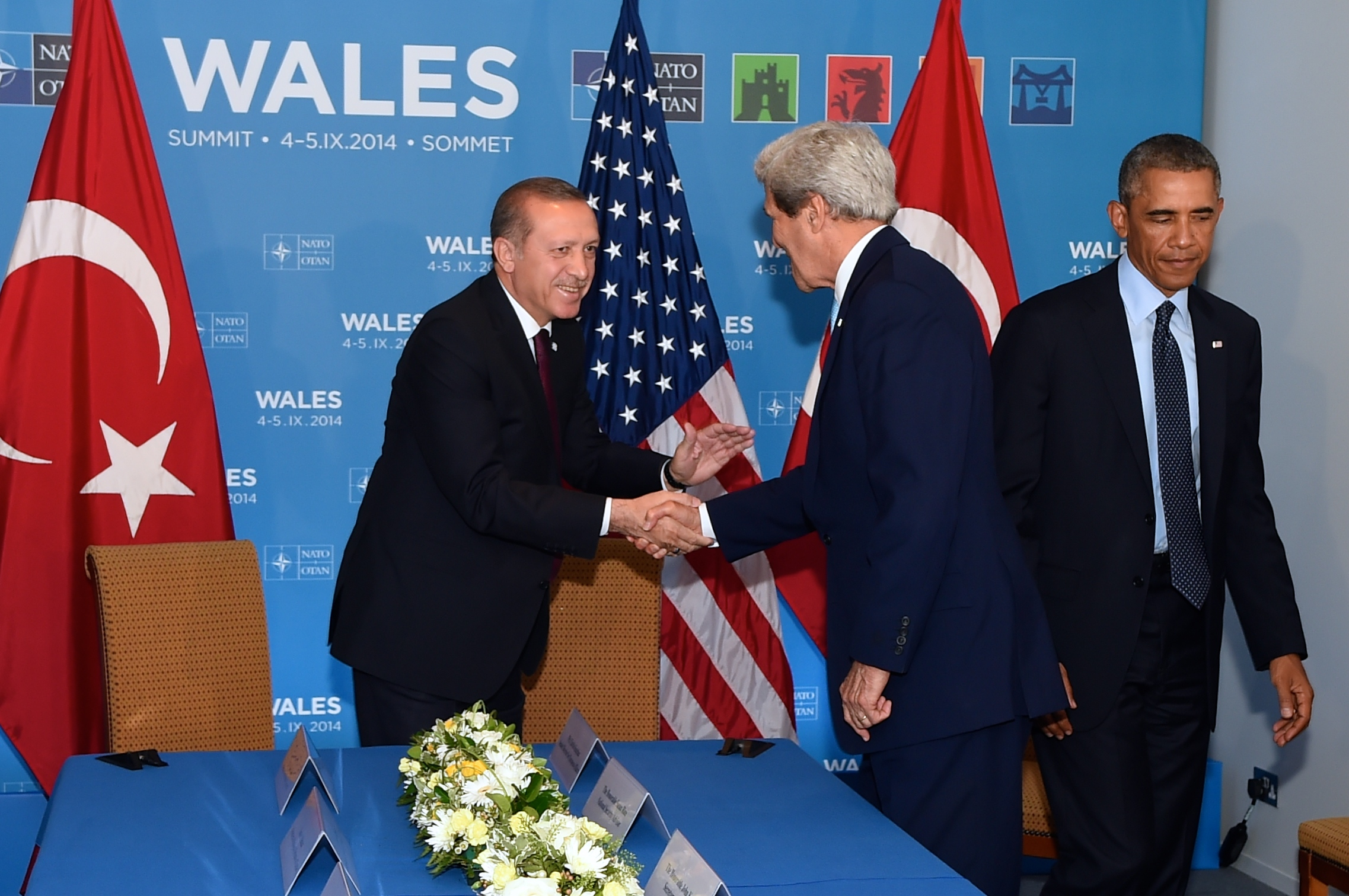 Click photo to download. Caption:U.S. Secretary of State John Kerry (center) shakes hands with Turkish President Recep Tayyip Erdogan (left) before joining President Barack Obama (right) for a bilateral meeting between the leaders on the sidelines of the NATO Summit on Sept. 5, 2014 in Newport, Wales, United Kingdom. Credit: State Department.