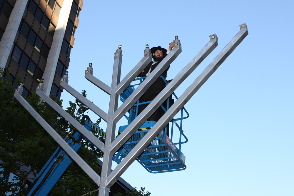 Click photo to download. Caption: A Chabad rabbi lights a public menorah in Sydney, Australia, in December 2012. Credit: Eva Rinaldi via Wikimedia Commons.