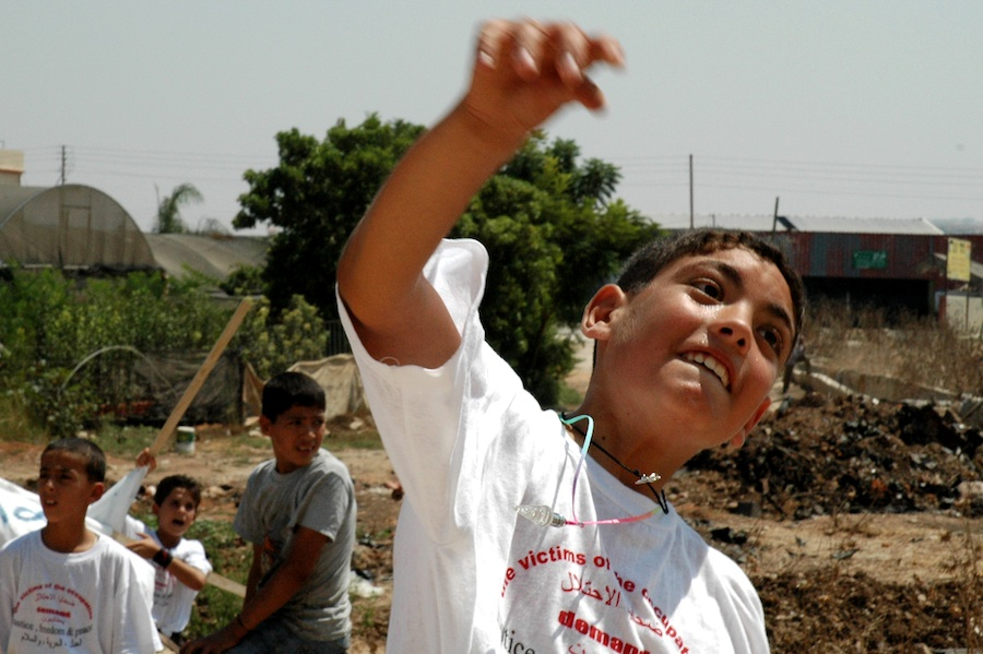 Click photo to download. Caption: A Palestinian boy throws a stone at Israel's security fence.Credit:JustinMcIntosh.
