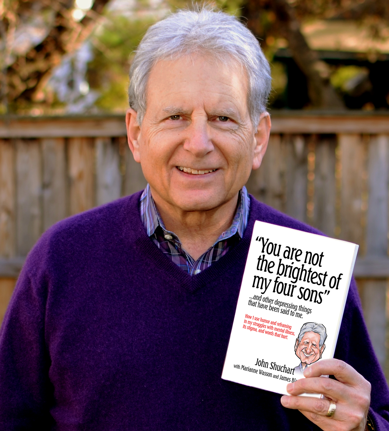 "Click photo to download. Caption: John Shuchart holds his recently self-published book, ""You are not the brightest of my four sons."" The book demonstrates how Shuchart uses humor and reframing in his struggles with mental illness, its stigma, and the words that hurt. Credit: Courtesy John Shuchart."