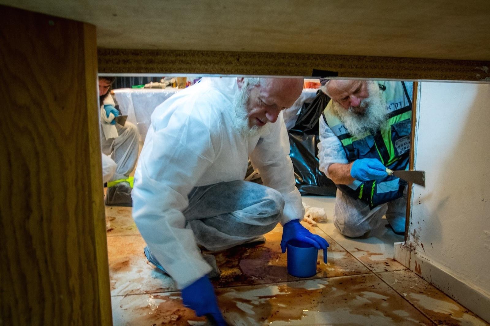 The ZAKA volunteer emergency response group—including its chairman, Yehuda Meshi Zahav (center)—cleans up the scene of Friday night's deadly Palestinian terror attack at the Salomon family home in Halamish. Credit: Yehezkiel Itkin/ZAKA.
