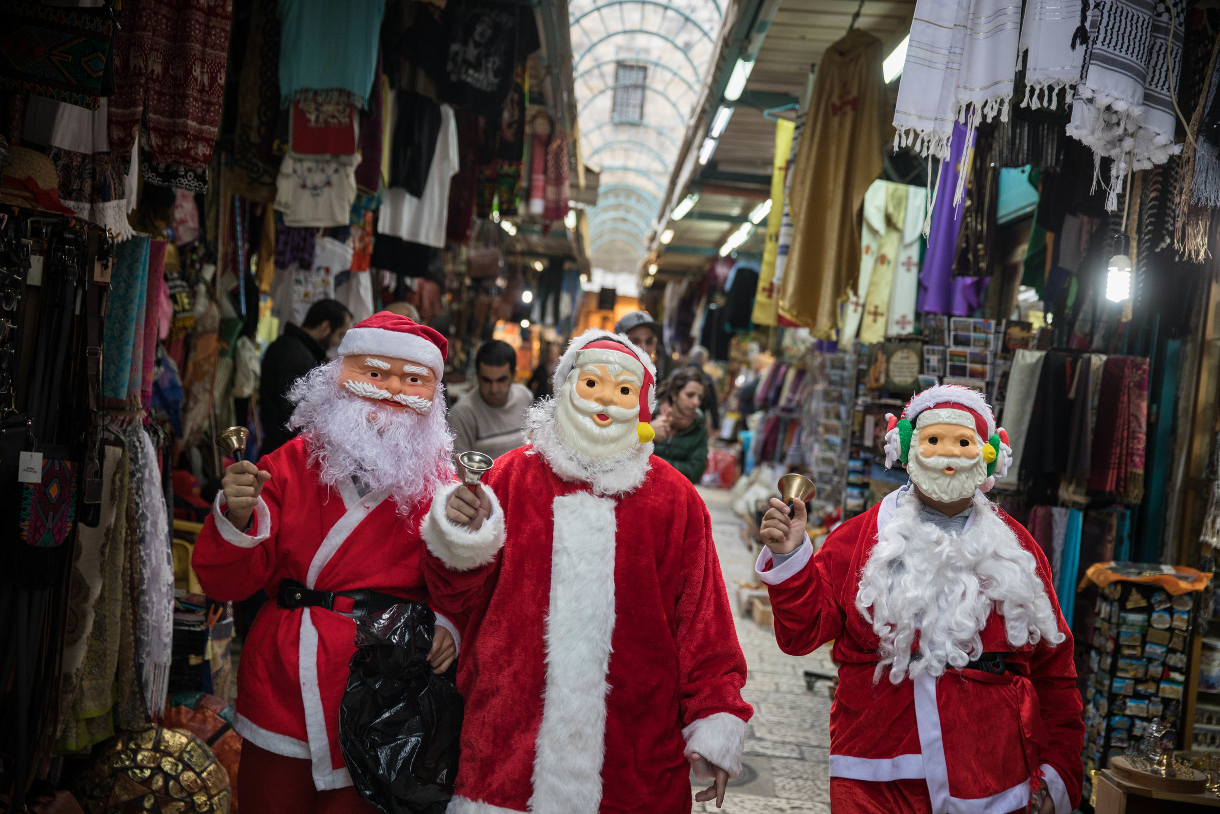 People dressed up as Santa Claus walk through the market in Jerusalem's Old City on Christmas eve, Dec. 24, 2017. Credit: Hadas Parush/Flash90.