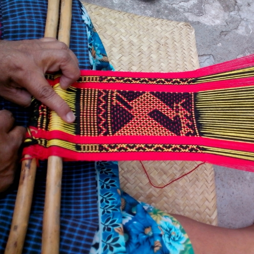 Crispina demonstrating backstrap loom weaving