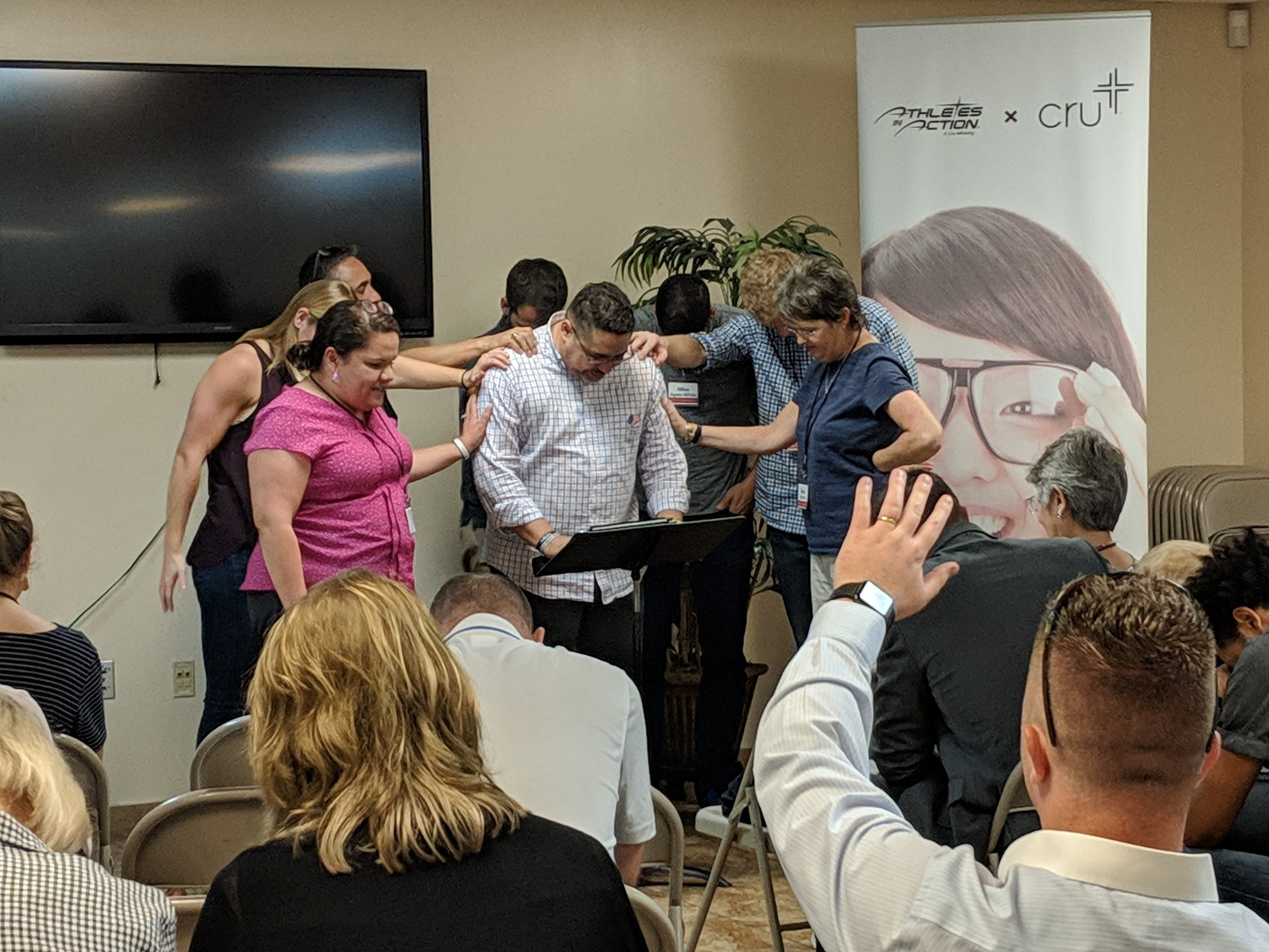 Michelle (in pink) leads a time of prayer for a local partner at the Lenses Institute in Orlando.