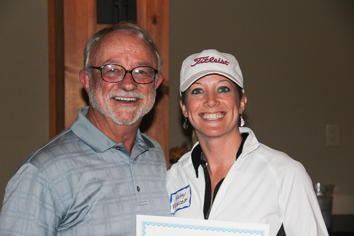 Kathy Fauscett receives award for women's longest drive and closest to pin from Kanute Rarey