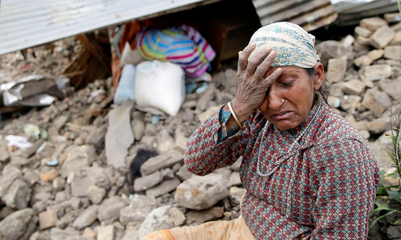 An elderly woman mourns in front of her destroyed home in the Kumalpur village, on the outskirts of capital Kathmandu. Photograph: Narendra Shrestha/EPA (from The Guardian)