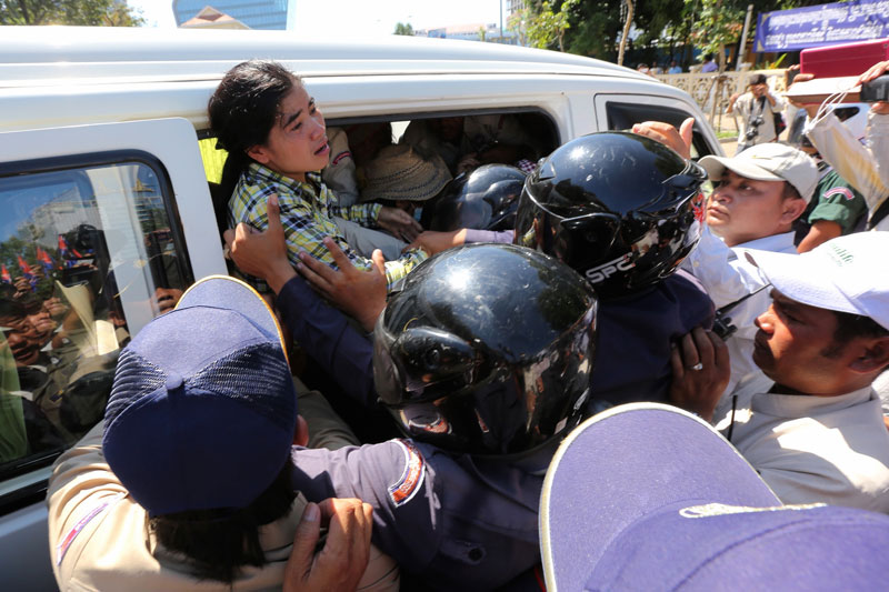 Physically tiny but courageous Cambodian activist, Tep Vanny, being arrested by Cambodian police in riot gear.
