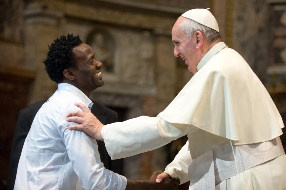 Pope Francis greets a refugee during a mass in the Church of the Gesu in Italy.