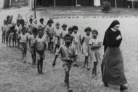A nun leads aboriginal children away