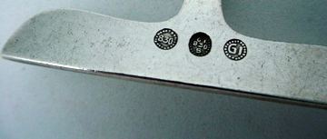 This is an example of the Classic GI marking inside a circle of beads (used from 1915-1930), as well as the .830 mark used before 1927, denoting the 83% silver content used before going to the sterling standard. Also present is the GI 830S mark as well. Often earlier pieces could be stamped multiple times.